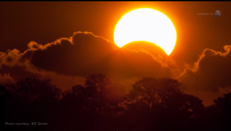 Eclipse parcial de Sol nubes arboles