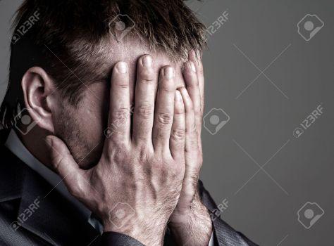 18103981-exhausto-triste-hombre-de-negocios-que-cubre-su-rostro-con-las-manos-foto-de-archivo